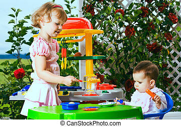 kids and toy kitchen - a 6 month old baby and a 4 years old...