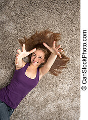 Relaxed woman lying on floor indoors and holding hands up...