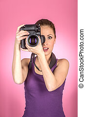 Pretty professional photographer using camera. Young woman holding camera against pink background