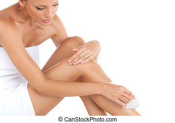 depilation of female legs with waxing on white background. closeup of young woman getting legs waxed for hair removal