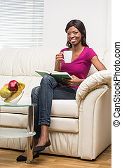 Portrait of relaxed young woman reading book. beautiful girl sitting on sofa at home indoor and smiling