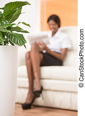 blurred young black girl with laptop computer. Woman sitting in bright living room with plant on foreground