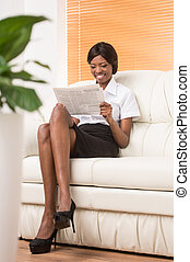 full image of young black girl with laptop computer. Woman sitting in bright living room with plant on foreground