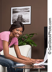 young african girl learning at home and smiling. pretty...