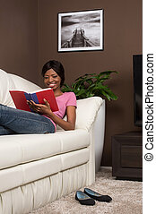 Beautiful youthful woman relaxing at home on couch. Young woman on sofa reading novel