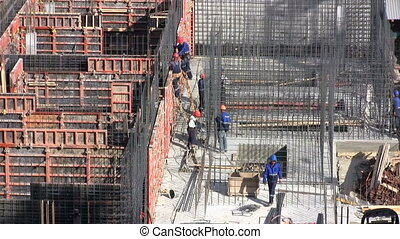 Workers on a construction site set reinforcement for...