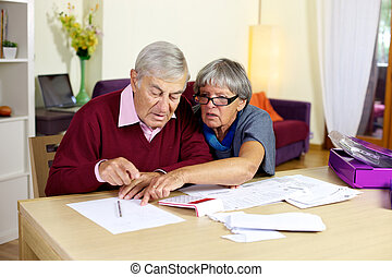Senior couple in trouble calculating bills and taxes -...