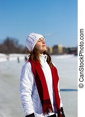 Winter portrait of an attractive woman soaking in the sun -...