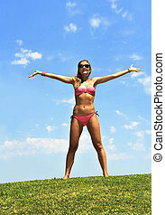 happy young woman in bikini opening arms to the air in summer sky