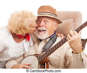 Kiss for Grandpa - Senior man playing banjo for his lady is...