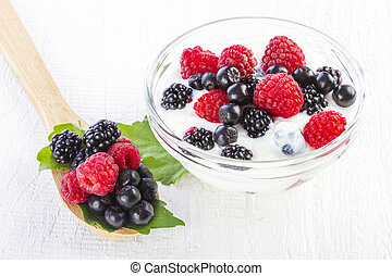 yogurt with forest berries in bowl on white wooden...