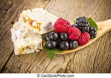 muesli bars with fresh berries on wooden background