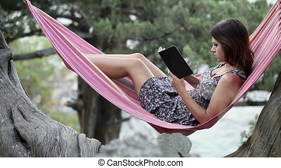 Woman in hammock on tablet