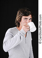 Handsome young man isolated over black drinking coffe
