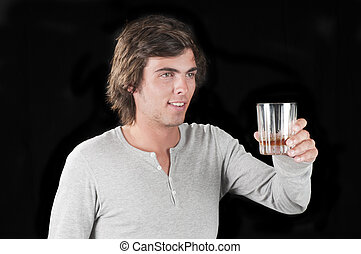 Handsome young man isolated over black with a glass of whiskey