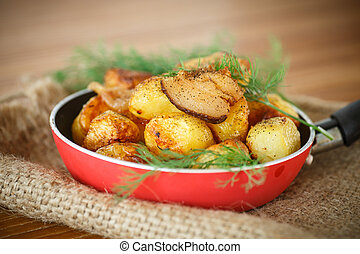 fried potatoes with slices of bacon in a frying pan