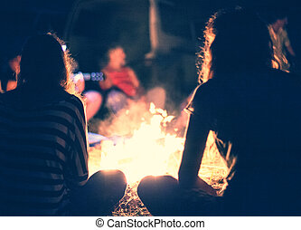 People near a bonfire - People sit at night round a bright...