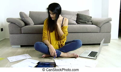 Woman dealing with taxes - Sad woman reading taxes and bills