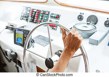 Driving boat - Close up captain hand on boat steering wheel