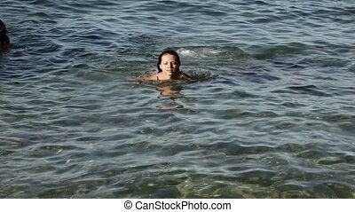 Girl swimming in sea - Skinny girl floating in clear sea