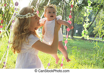 Happy mother and baby girl having fun outdoor