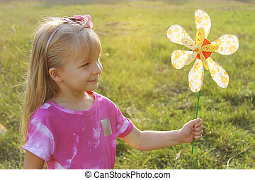 Girl with colorful pinwheel in sunset light