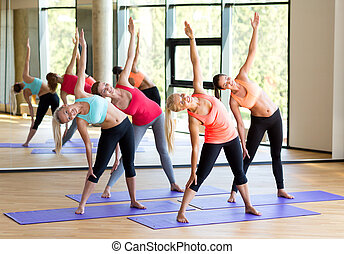 group of smiling women stretching in gym - fitness, sport,...