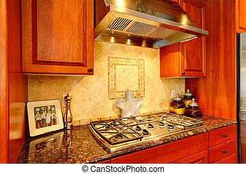 Kitchen cabinet with granite top and built-in stove. View of...