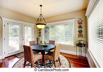 Dining room with round black table and wicker chairs