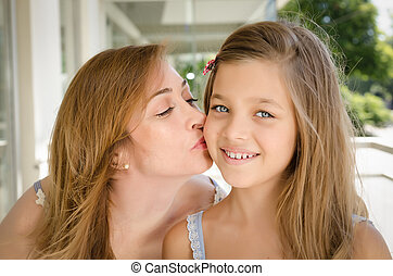 Mother kissing her daughter in the cheek Taken in Buenos...