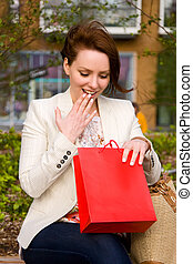 young woman looking at a gift in a bag
