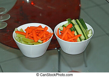 Crudites of carrots, celery and cucumber on a glass table