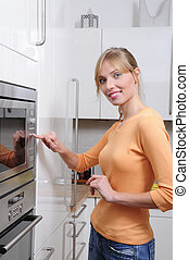 Blond woman cooks with a microwave in a modern kitchen