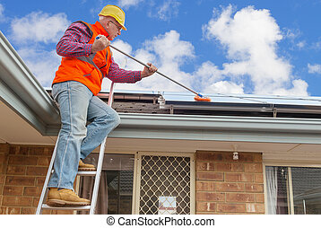 worker and solar panels - experienced worker cleaning solar...