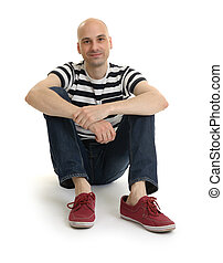 Full length portrait of a stylish young man sitting over...