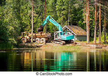 Blue excavator clears the shore of the lake