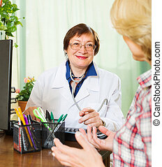 Mature doctor consulting female patient