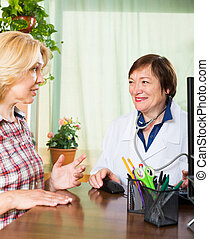 woman and doctor discussing medical issues - Elderly woman...