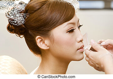Applying makeup. - Bridal applying cosmetic with applicator....