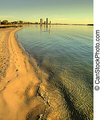 Shoreline To Buildings - Beach shoreline stretches away in...
