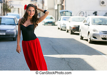 Spanish woman in black dress is posing in the town