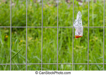 Plastic waste is disposed of irresponsibly on wire cage