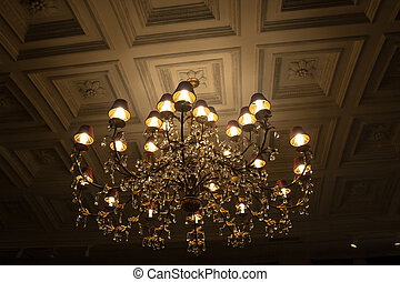 shining chandelier hanging on a ceiling in restaurant