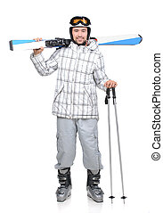 Skiing - Handsome active man with sky in ski suit. Standing...
