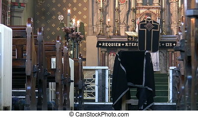 Priest celebrating funeral mass - Priest in black vestments...