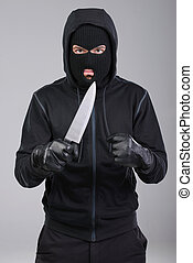 Criminality - Masked man aims with knife on gray background