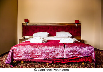 double bed in luxury hotel room with towels and bathrobe