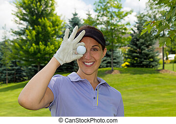 Female golfer holding a golf ball over her eye