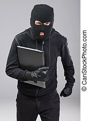 Criminality - Thief stealing a laptop computer. Isolated on...