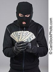 Criminality - Robber in a mask rejoice stolen money. Gray...